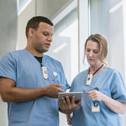 two nurses in blue scrubs reviewing mobile device